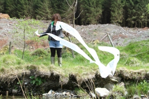 Ess stands on a grassy bank of a stream, wearing a green hoodie, leather jacket, cut-off denim shorts, black leggings and green wellies. They are a white human with short brown curly hair. They are holding both ends of a long strip of white paper or fabric which has caught in the wind and is twisting, looping and blowing away from them to the right, out over the stream.