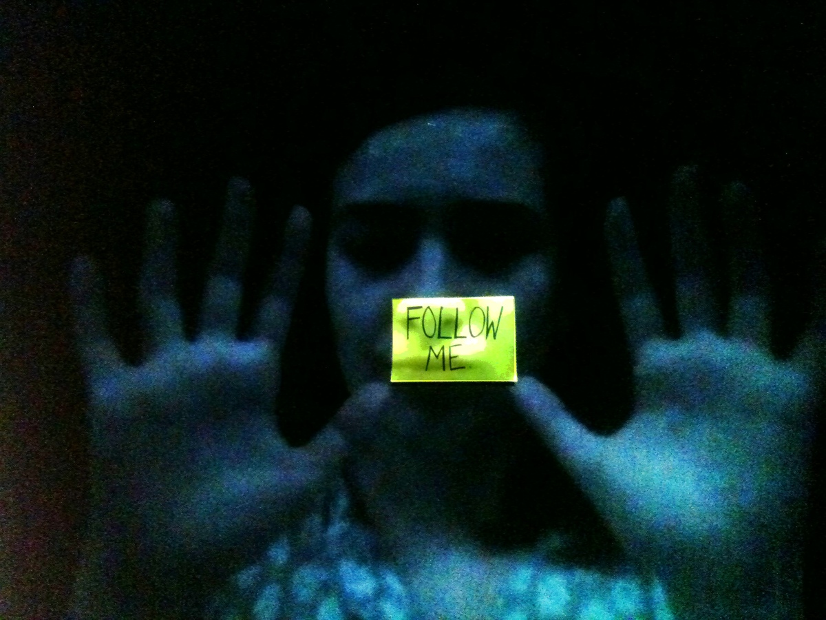 "A grainy blue projected image of Alicia's face, palms held up and out towards us on either side of Alicia's face. In the centre is a yellow postit note, part of the surface being projected onto. It reads ""Follow me"""