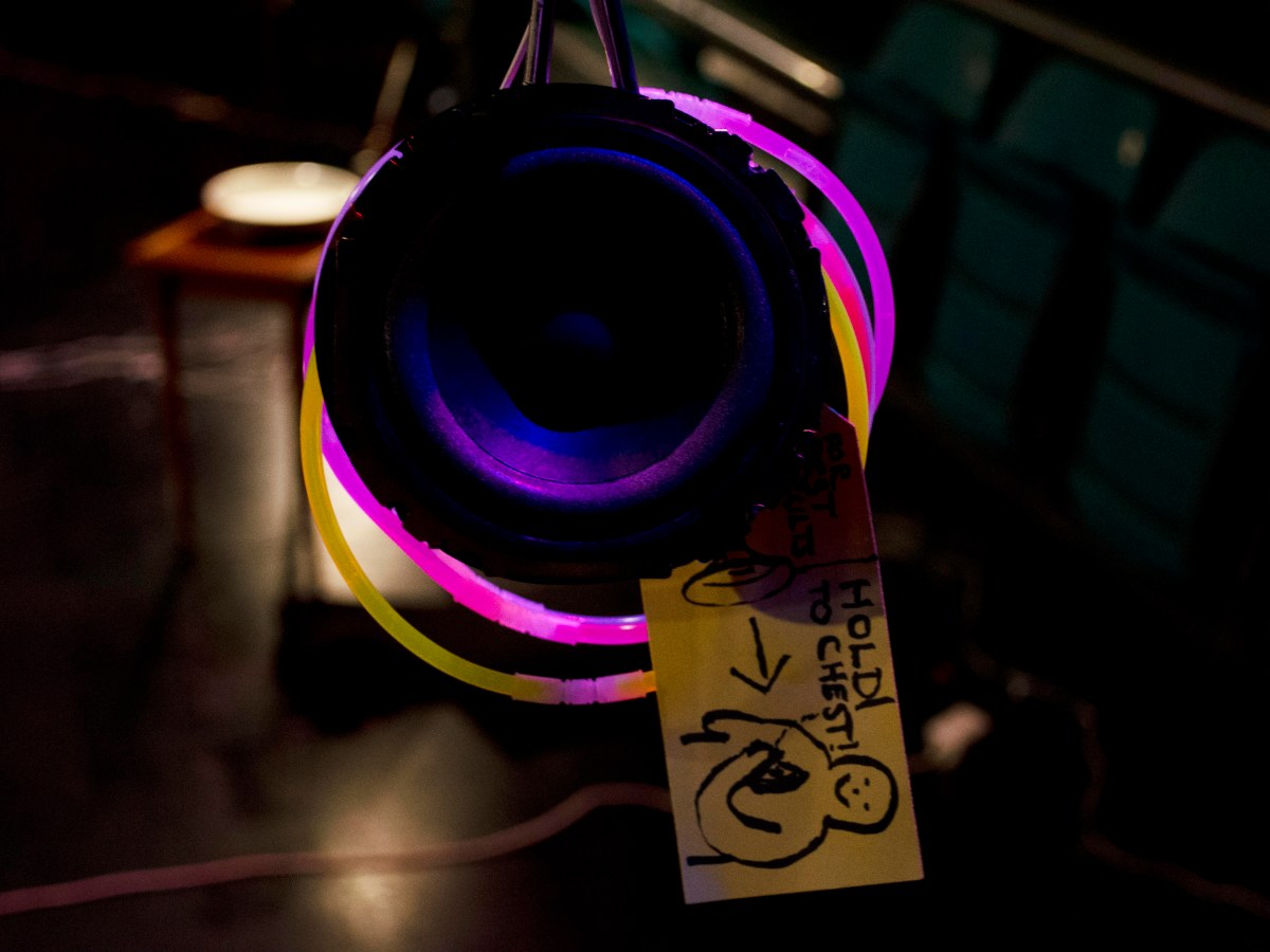 """A bare speaker cone hanging down, with glow-stick bracelets encricling it. A card tag hangs off it, showing a catrtoon figure holding a speaker to their chest, and the words """"hold to chest"""" are written beside it."""