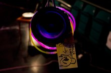 "A bare speaker cone hanging down, with glow-stick bracelets encricling it. A card tag hangs off it, showing a catrtoon figure holding a speaker to their chest, and the words ""hold to chest"" are written beside it."