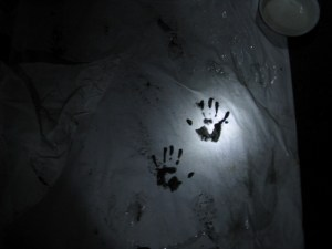 Two black handprints show up on a crumpled white surface, spotlit in torchlight.