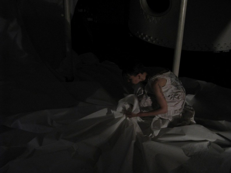 It is very dark. In the darkness a slim white figure is hunched overgrasping part of a great swathe of dirty white paper. They seem to be in some kind of industrial space with metal poles, and they are wearing a dirty white nightdress.