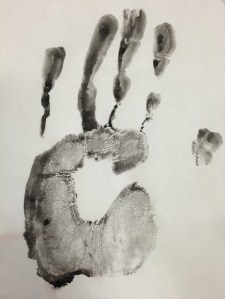 A palm print made with black ink or paint on white paper.