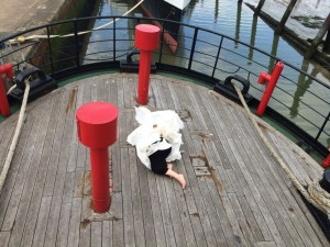 Looking down onto the wooden deck of a ship, with red vent pipes and a black railing around the edge. In the centre of the deck a figure is lyng down, almost completely hidden under and inside ca crumpled paper garment. One leg sticks out the bottom - it is a white persons leg, bare up to the knee and then wearing black trousers above. Some water reflecting blur sky is visible beyond the deck and railings.