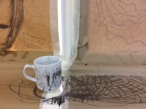 A mug on a windowsill. The wall and window is comepltely covered in brown paper which has been scribbled all over. The mug has also been drawn on the whole picture is covered in doodling lines and marks.