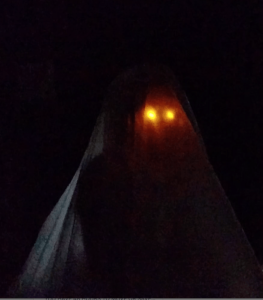 In the darkness is a shrouded figure - we can just make out their form. All that's really visible is glowing fire eyes