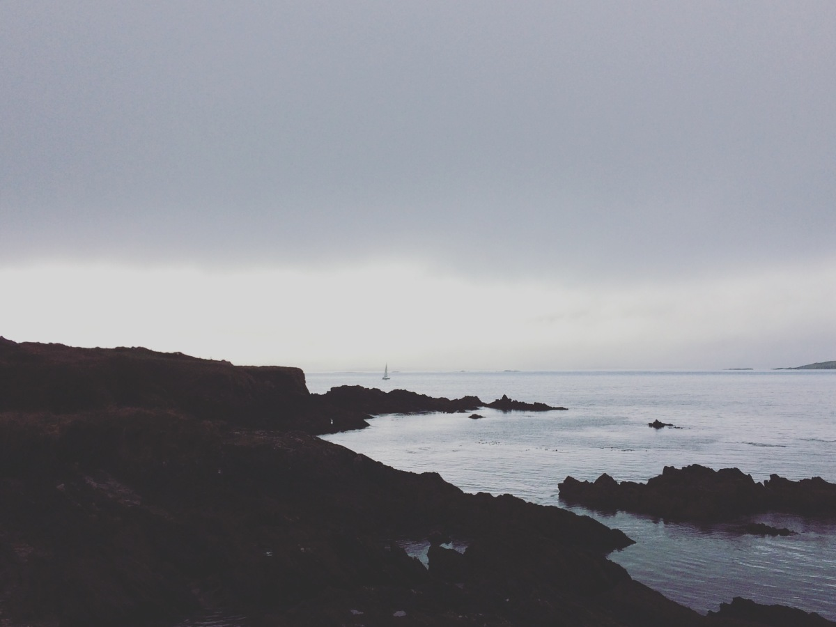 A rugged rocky coastline with a grey, overcast but softly beautiful sea gently rolling in against the ragged black edges of rocks.