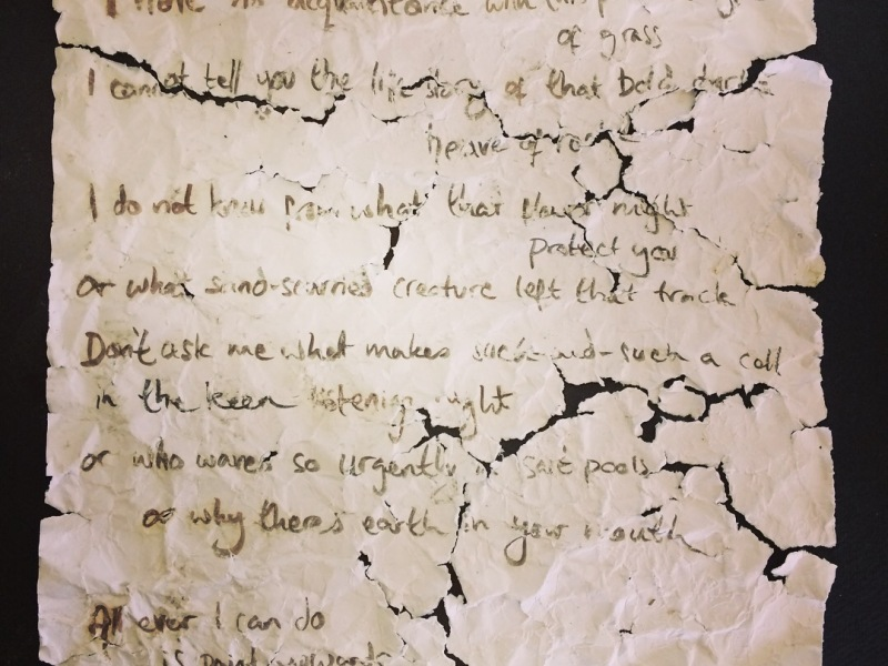 A handwritten poem on a piece of paper that has been washed, crumpled, ripped and pieced back together.